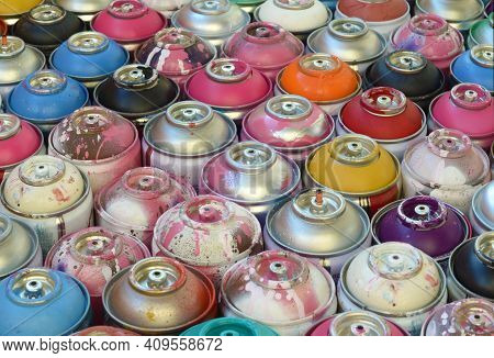 Large Number Of Used Colorful Spray Cans Of Aerosol Paint Lying On The Treated Wooden Surface In The