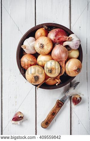 Bowl With Onions And Garlic On A White Wooden Background.