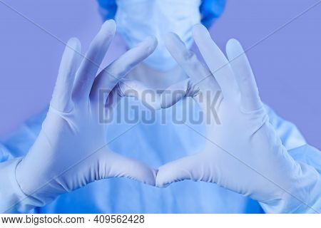 Female Doctor Or Nurse In Medical Mask And Protective Gloves Shows The Symbol Of The Heart. Love, Ca