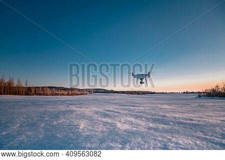 Drone flying above field covered with snow on sunny winter day