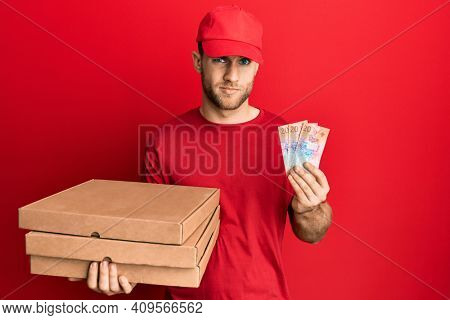Young caucasian man holding delivery box and swiss franc banknotes skeptic and nervous, frowning upset because of problem. negative person.