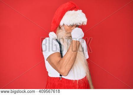 Old senior man with grey hair and long beard wearing white t-shirt and santa claus costume smelling something stinky and disgusting, intolerable smell, holding breath with fingers on nose. bad smell