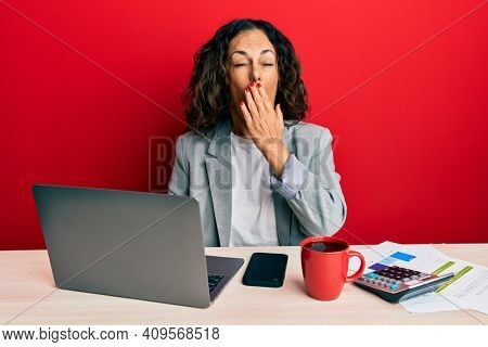 Beautiful middle age woman working at the office drinking a cup of coffee bored yawning tired covering mouth with hand. restless and sleepiness.