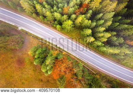 Aerial View Og Curvy Road Between Evergreen Forest With Green Pine Trees In Summer Mountains.