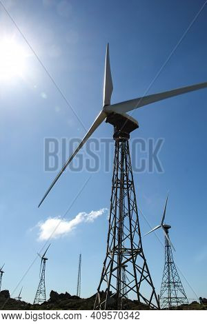 Wind Turbines In The South Of Spain. Alternative Energy Sources. Wind Turbine Masts Against The Blue