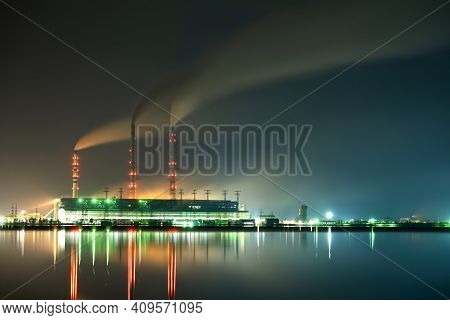 Brightly Illuminated Coal Power Plant High Pipes With Black Smoke Moving Upwards Polluting Atmospher