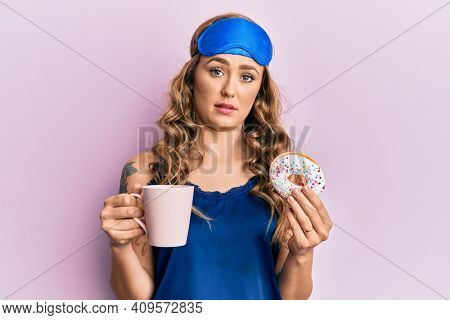 Young blonde girl wearing sleep mask and pyjama having breakfast clueless and confused expression. doubt concept.