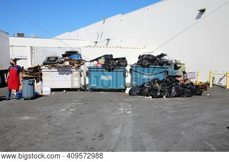 Lake Forest, California - USA - February 22, 2021: Industrial Trash Cans overflowing with trash and recyclable waste. Garbage Cans filled with garbage ready to be hauled to the dump. Editorial Use.