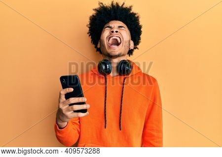 Young african american man with afro hair using smartphone angry and mad screaming frustrated and furious, shouting with anger looking up.