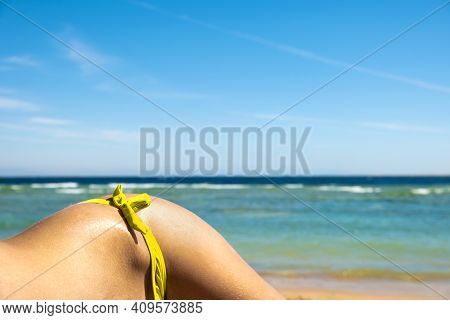 Close Up Of Young Woman Hip And Shoulder Laying On Beach Chair At Sea Shore Sunbathing.