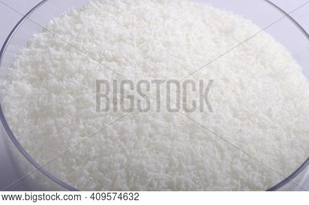 Grated coconut in round bowl. Top view, isolated on white.