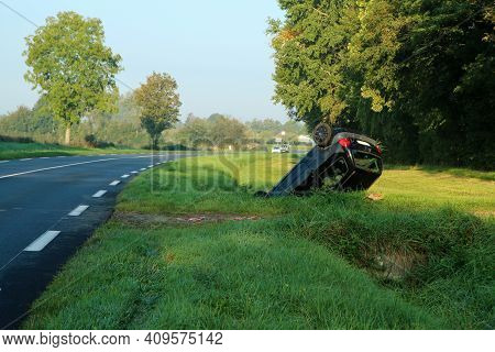 Abandoned Car In The Ditch After The Traffic Accident. Lying On The Roof.