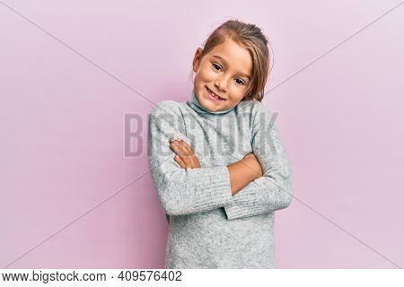Little beautiful girl wearing casual turtleneck sweater happy face smiling with crossed arms looking at the camera. positive person.