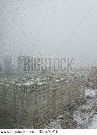 Texture Of Frozen Window Glass With Mysterious City View Behind. Defocused Cityscape While Frosty Ra