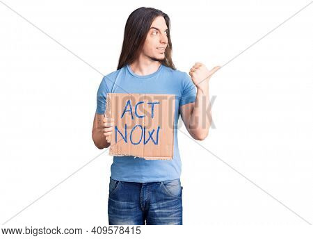 Young adult man with long hair holding act now banner pointing thumb up to the side smiling happy with open mouth