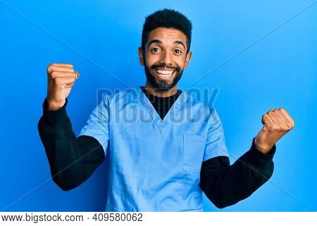 Handsome hispanic man with beard wearing blue male nurse uniform screaming proud, celebrating victory and success very excited with raised arms