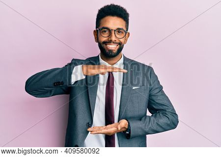 Handsome hispanic business man with beard wearing business suit and tie gesturing with hands showing big and large size sign, measure symbol. smiling looking at the camera. measuring concept.