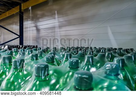Drinking Water In Plastic Bottles Packed In Polyethylene Packaging And Put Up For Sale In A Shopping