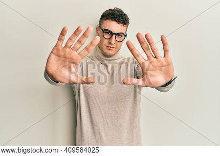 Hispanic young man wearing casual turtleneck sweater doing frame using hands palms and fingers, camera perspective