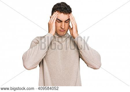 Hispanic young man wearing casual turtleneck sweater suffering from headache desperate and stressed because pain and migraine. hands on head.