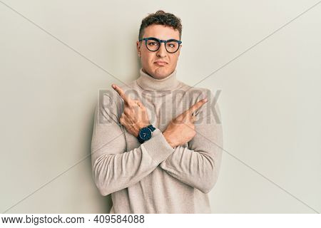 Hispanic young man wearing casual turtleneck sweater pointing to both sides with fingers, different direction disagree