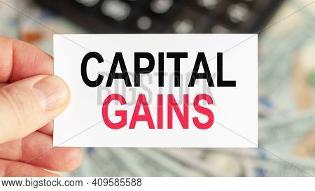 Motivational Words: Capital Gains. Man Holds A Piece Of Paper With The Text: Capital Gains. Business