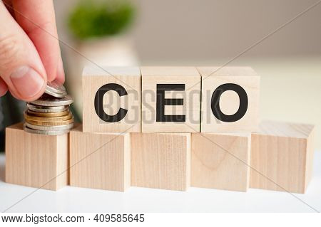 The Word Ceo Written On Wood Cubes. A Man's Hand Places The Coins On The Surface Of The Cube. Green