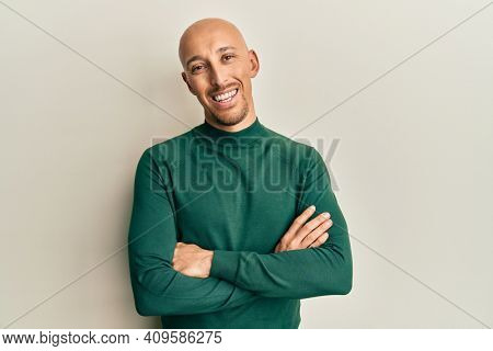 Bald man with beard wearing casual turtleneck sweater happy face smiling with crossed arms looking at the camera. positive person.