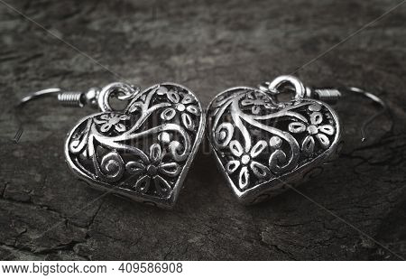 Silver Earrings In The Form Of Hearts On A Wooden Background. Bijouterie Earrings Close Up