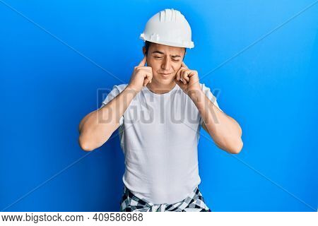 Handsome young man wearing builder uniform and hardhat covering ears with fingers with annoyed expression for the noise of loud music. deaf concept.