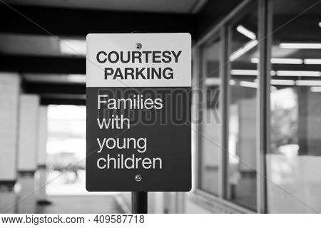 Parking Sign. Courtesy Parking - Families with young children. Red and White Courtesy Parking Sign. Black and White.