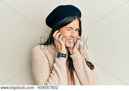 Young brunette woman wearing french look with beret covering ears with fingers with annoyed expression for the noise of loud music. deaf concept.