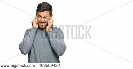 Handsome hispanic man wearing casual clothes covering ears with fingers with annoyed expression for the noise of loud music. deaf concept.