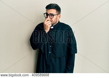 Young hispanic man wearing priest uniform standing over white background smelling something stinky and disgusting, intolerable smell, holding breath with fingers on nose. bad smell