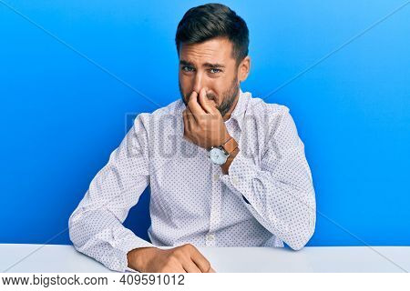 Handsome hispanic man wearing business clothes sitting on the table smelling something stinky and disgusting, intolerable smell, holding breath with fingers on nose. bad smell