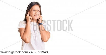 Beautiful caucasian woman wearing casual white tshirt covering ears with fingers with annoyed expression for the noise of loud music. deaf concept.