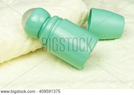 Bottle Of Roll On Antiperspirant Deodorant Lying On The Background Of Bath Towels. Personal Hygiene