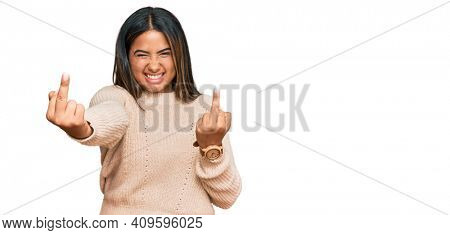 Young latin girl wearing wool winter sweater showing middle finger doing fuck you bad expression, provocation and rude attitude. screaming excited