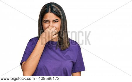Young hispanic girl wearing casual purple t shirt smelling something stinky and disgusting, intolerable smell, holding breath with fingers on nose. bad smell