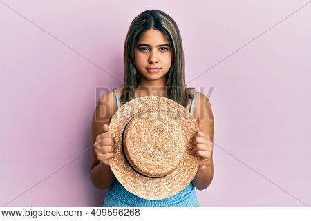 Young latin woman holding summer hat relaxed with serious expression on face. simple and natural looking at the camera.
