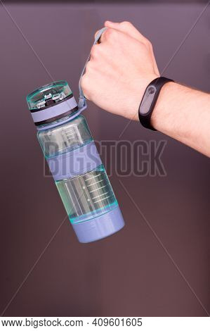 Hand Holds Sporty Bottle Of Water Or Sport Drink, Brown Background. Bottle Of Water In Male Hand Wit