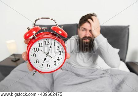 Tips For Becoming An Early Riser. Man Bearded Hipster Sleepy Face In Bed With Alarm Clock. Problem W