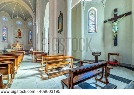 ALBA, ITALY - JUNE 23, 2020: View of cross and pews in the nave of Divin Maestro - a roman catholic parish church recently renovated, located in small town of Alba in Piedmont, Northern Italy.