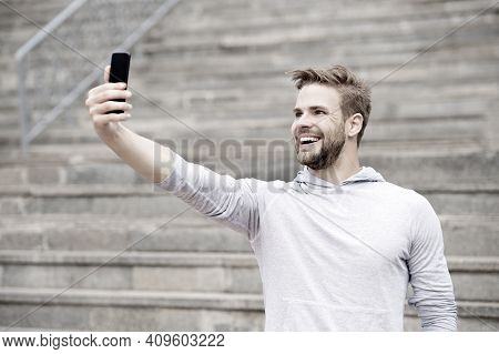 Man With Beard Walks With Smartphone, Urban Background With Stairs. Man Blogger Using Video Conferen