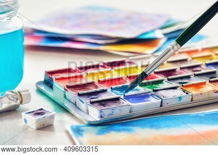 Set Of Watercolor Paints, Paintbrush, Glass Of Water And Paper Sheets Of Watercolor Paintings On Bac