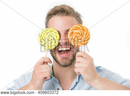 Man Holds Big Lollipops On Eyes As Eyeglasses. Sweet Tooth Concept. Guy On Smiling Face Holds Two Gi