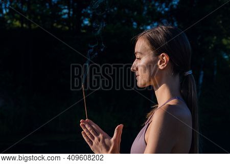 Woman Doing Yoga And Meditating In A Sunrise Outdoors, Holding Aroma Stick In Her Hands, Palms In Na
