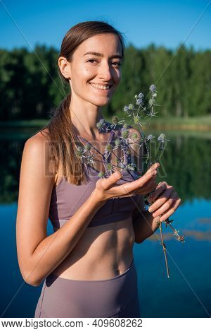 Young Tender Brunette Girl With A Herbal Branch In Front Of Her Face Standing Near The Lake.