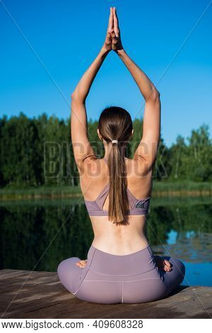 Young Female Practicing Yoga Against The Sky On A Sunrise. Pretty Slim Woman Performs An Exercise. H