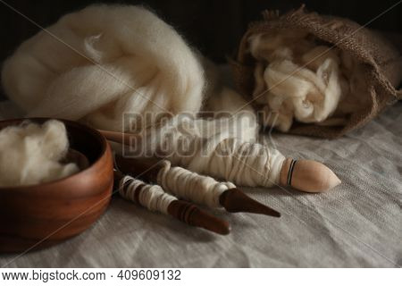 Soft White Wool And Spindles On Table, Closeup